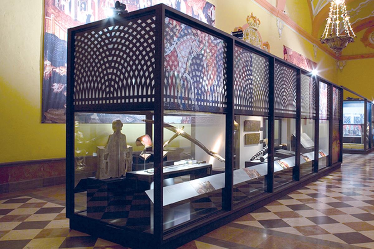 Vitrina central en el Salón de los Tapices. Entre las piezas expuestas una Ballesta del periodo nazarí procedente de la Alpujarra granadina formada por dos piezas.