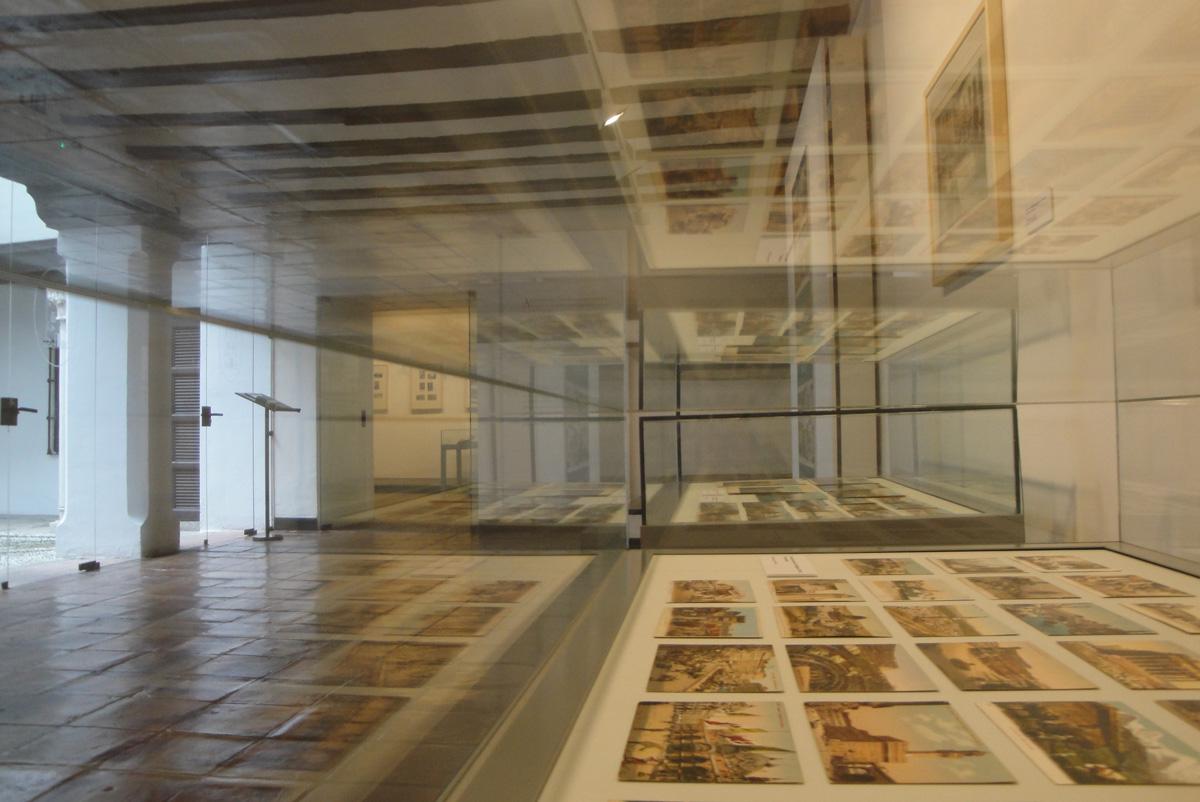 Vista desde un lateral de vitrina tanto de uno de los espacios expositivos del Museo Casa de los Tiros como del interior de la vitrina que contiene postales a color.