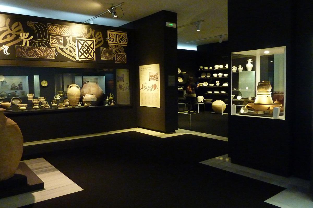 Vista general de la exposición. A la izquierda piezas procedentes del Museo de Almería, a la derecha, conjunto de marmita con tapadera, anafe-hornillo y brasero procedente de Madinat Ilbira (Granada) [Museo Arqueológico y Etnológico de Granada].