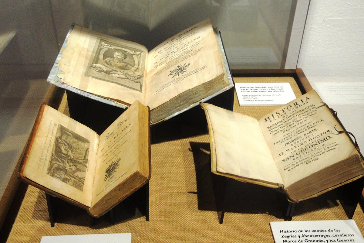 Vitrina con tres libros que contienen diferentes textos y crónicas de la época sobre la rebelión de las Alpujarras.