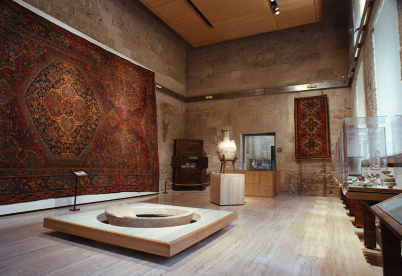 In the background, a Caucasian carpet (19th c.). The free-standing object is Fortuny-Simonetti Vase (14th c.). In the center of the hall, large circular fountain (4th c.), carved in white veined marble.