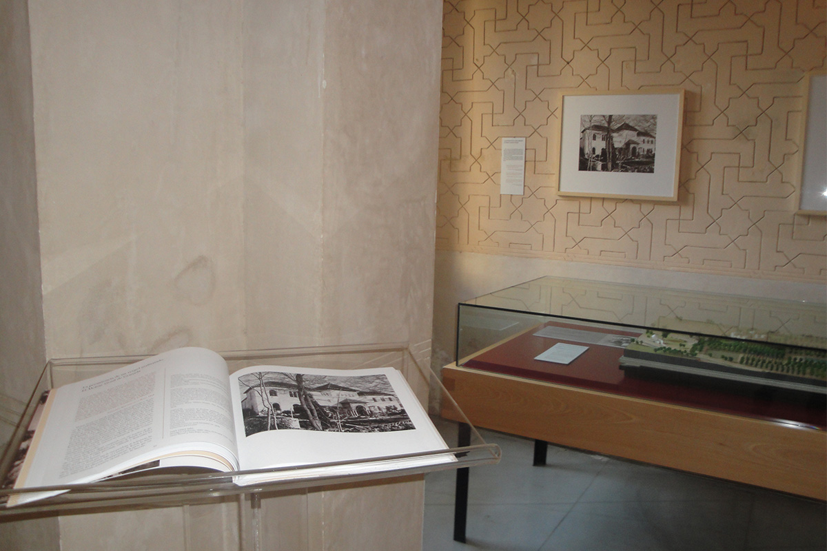 In the foreground, the exhibition catalogue showing a page representing Alcázar Genil, Granada