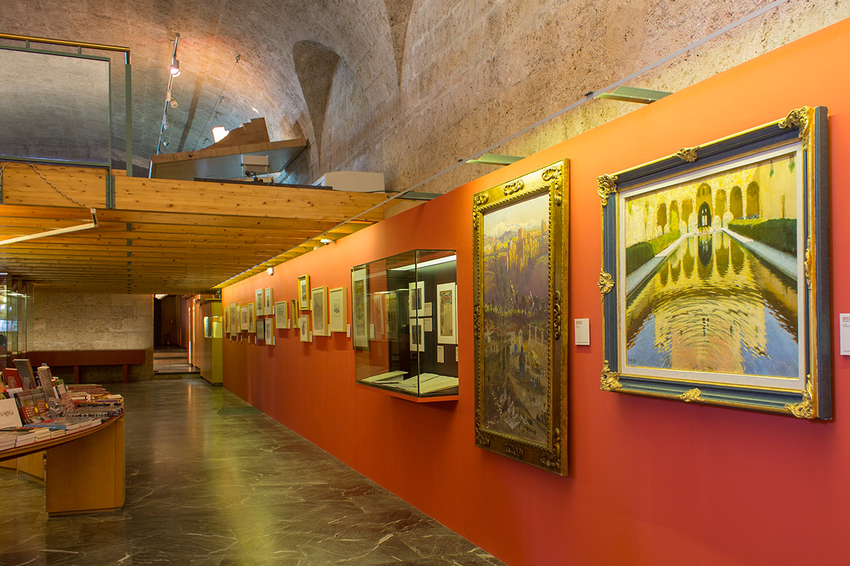View of an exhibition hall. In the foreground, picture showing the Arrayanes Court, by Eugenio Gómez Mir (20th century). Photo: Miguel Ángel Benavente Gálvez.